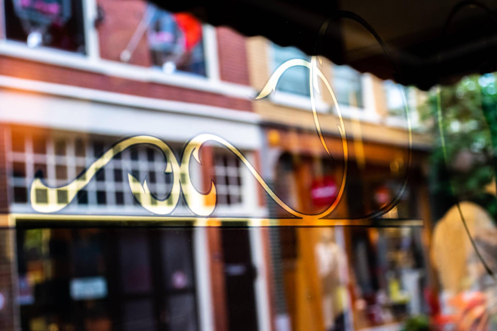 Bladgoud detail op raam kapperszaak
